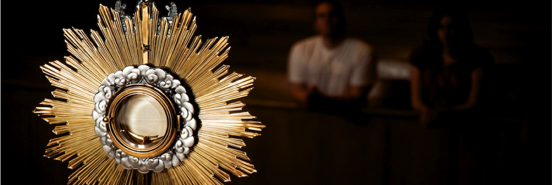 close up of monstrance with gentleman praying in background