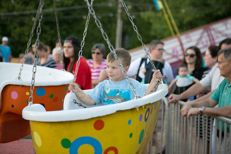 little kid riding a ride at the parish festival
